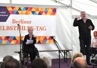 Foto Frau Bendzuck mit Grußwort und Gebärdensprachdolmetscher auf de Bühne